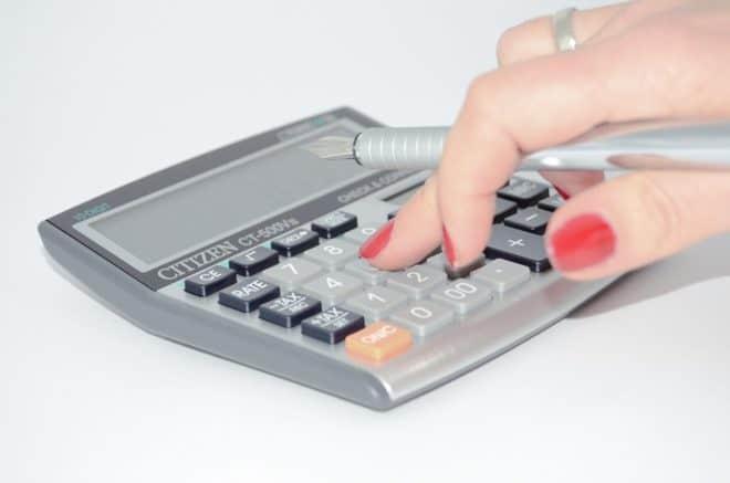 Une main tenant un stylo et effectuant un calcul sur une calculatrice